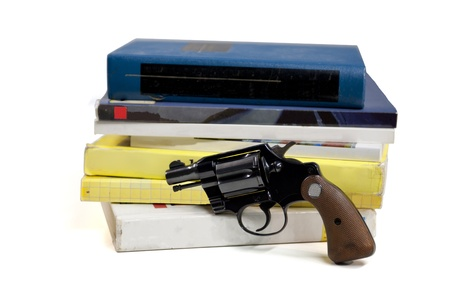 night school: A 38 caliber pistol stands in front of school textbooks, isolated on white, focus on gun handle