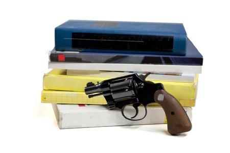 A 38 Kaliber Pistole steht vor Schulbüchern, isoliert auf weiß, auf Pistolengriff konzentrieren Standard-Bild - 12531088