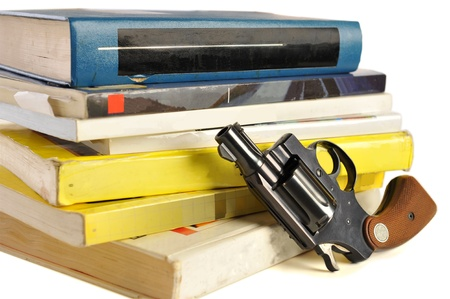 A 38 caliber pistol stands in front of school textbooks, isolated on white, focus on gun barrel Stock Photo