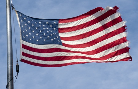 Tattered American flag flapping in the wind  on a blue sky with clouds Stock Photo - 12886904