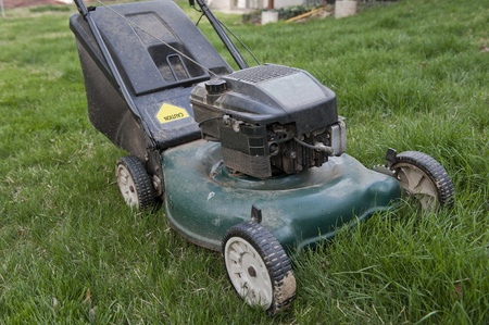 Horizontal shot of dirty lawnmower in overgrown grass photo