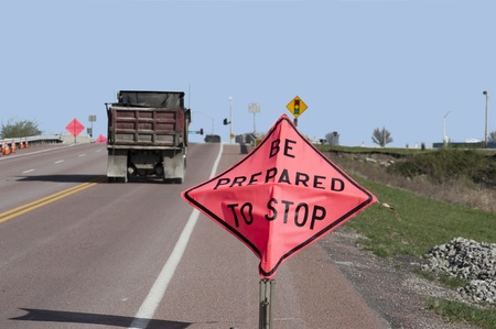 Sign saying  Be Prepared to Stop  bends with the wind as a dump truck speeds past it