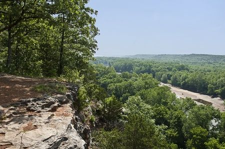 View of a lush green forest and riverbed from cliffs high above the trees