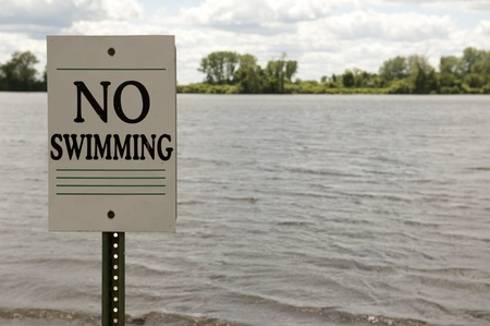 No Swimming sign posted on a lake shore Stock Photo