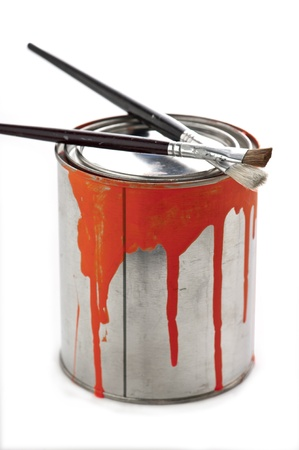 Two artists fine art paintbrushes resting on top of a paint can with orange paint dripping down the side of the can