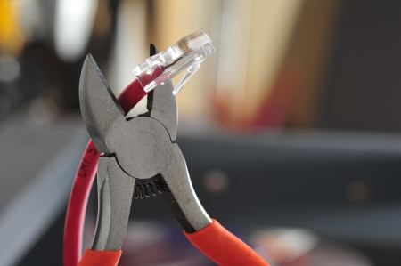 snip: Wire cutters with bright orange handles poised to snip the end off of a cat 5 computer networking cable Stock Photo