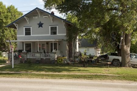 Der Hof eines ländlichen Heimat zeigt pure Americana-Stil mit einer erstaunlichen Vielfalt von Unordnung vom Bierdosen, Gitarre Fällen und Grill auf der Veranda zu den Fahrrädern hängen an Seilen in den Baum. Standard-Bild - 14500591