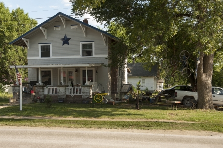 The yard of a rural home displays pure Americana style with an amazing variety of clutter from the beer cans, guitar cases and grill on the porch to the bicycles dangling from ropes in the tree. Editorial