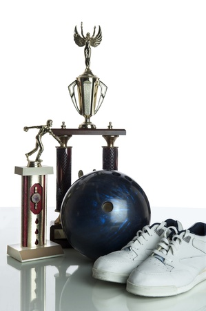 Bowling ball, shoes and trophies isolated on a white background and resting on a reflective white table top photo