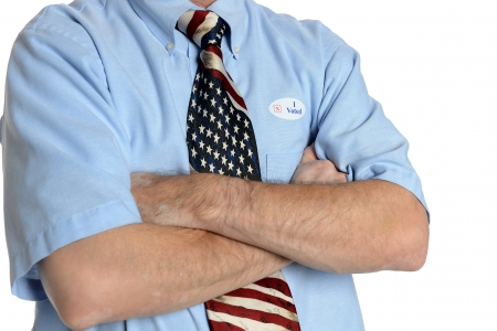 Patriotic voter wearing a U S  flag tie and dress shirt sports an  I voted  sticker