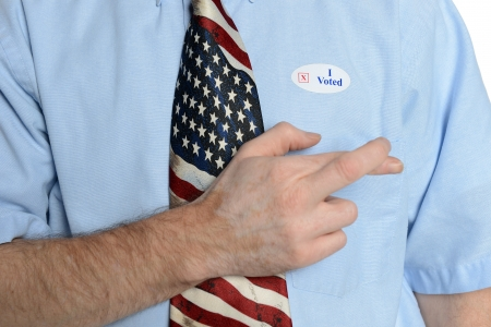 Patriotic voter wearing a U S  flag tie and dress shirt sports an  I voted  sticker crosses his fingers for good luck