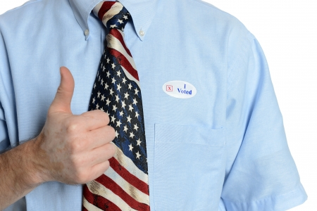 Patriotic voter wearing a U S  flag tie and dress shirt with an  I voted  sticker gives the  thumbs up  sign photo