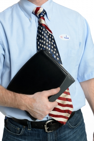 Patriotic voter wearing a U S  flag tie and dress shirt sports an  I voted  sticker photo