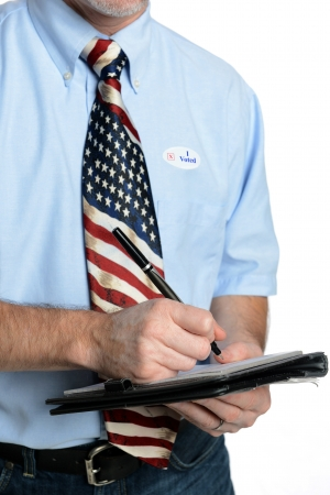 Patriotic voter wearing a U S  flag tie and dress shirt sporting an  I voted  sticker takes a poll photo