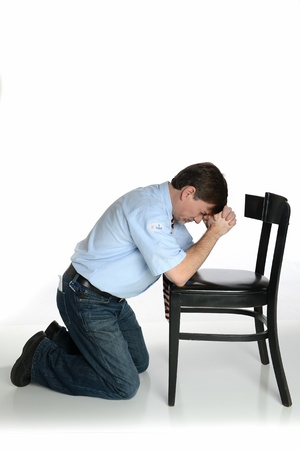 Man with  I Voted  Sticker kneels in prayer, isolated on white