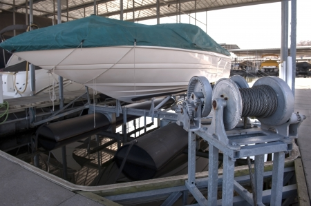 Expensive pleasure boat safely stored under canopy on a hyrdolic lift in a dock
