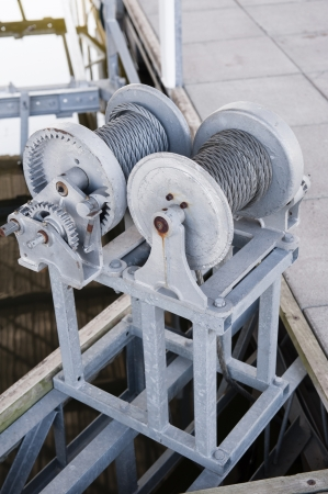 dockside: Cables and gear assembly for a boat lift in a dock Stock Photo