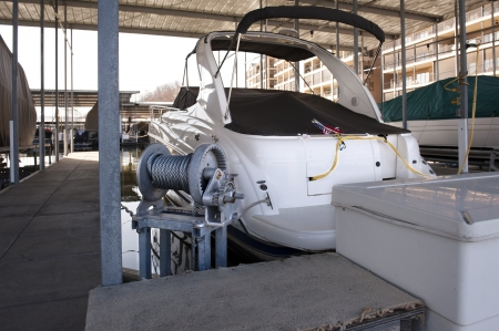 Expensive pleasure boat safely stored under canopy in a dock
