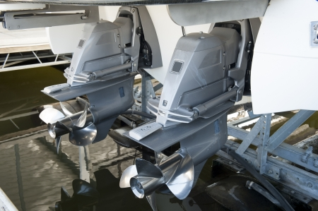 Twin motors suspended from an expensive pleasure boat safely stored on a hyrdolic lift in a dock Stock Photo