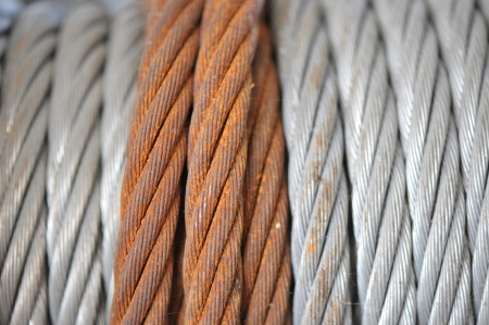 a rusty braded cable overlaps coils of newer steel cable