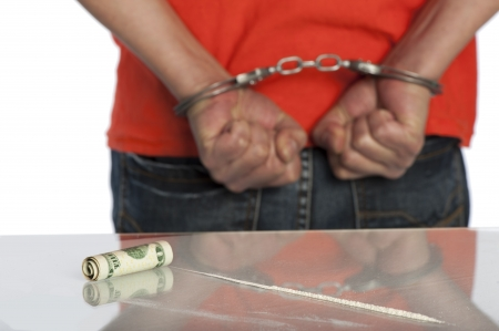 Man in handcuffs next to a table with a line of cocaine on it, selective focus on the  20 bill used for snorting
