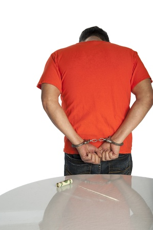 Man in handcuffs next to a table with a line of cocaine on it Stock Photo