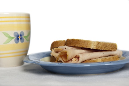 Closeup of a turkey sandwich on a brightly colored plate accompanied by a festive cup