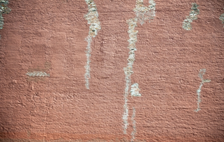 Old weathered red brick wall with streaks of white stain
