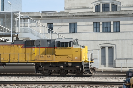 Closeup of a freight train engine passing a concrete building and stairway leading to the tracks Stock Photo - 19995358