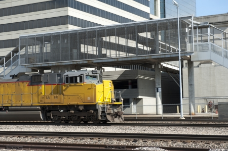 Train engine passes an office building and station stop Stock Photo - 19995361