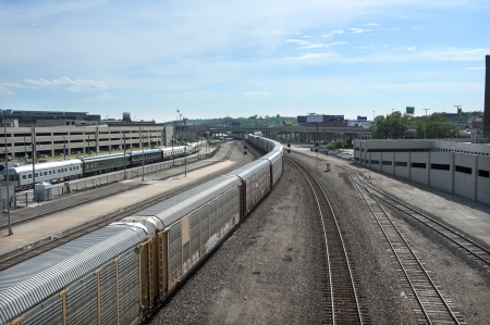 Freight train snakes through a city, under an overpass and off into the woods