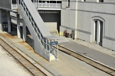 stairwell: Industrial train platform and outdoor stairwell between two sets of tracks