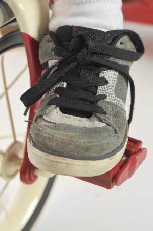 Closeup of a child's foot and shoe on a red tricycle pedal on a white Stock Photo - 23312041