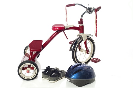 Red childs tricycle on a white
