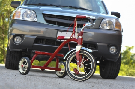 Childs tricycle dangerously parked in front of a large SUV photo