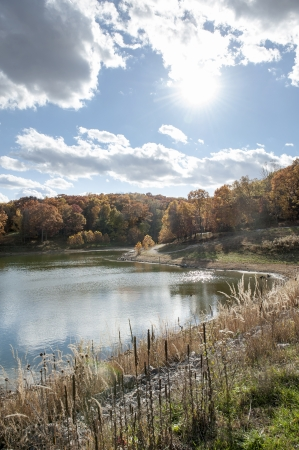 Shoreline of a peaceful lake surrounded by trees in fall colors Stock Photo - 23832365