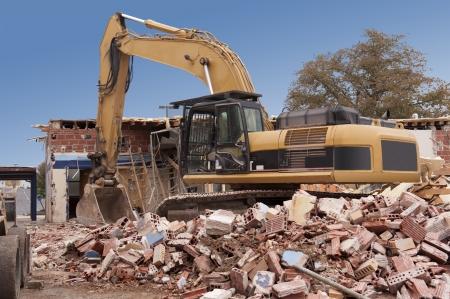 A large backhoe demolishes an old building