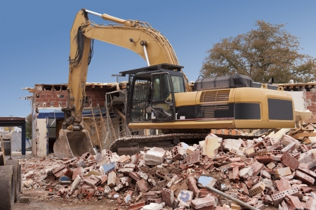 A large backhoe demolishes an old building Stock Photo - 23832366
