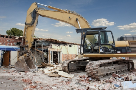 excavator: A large backhoe demolishes an old building