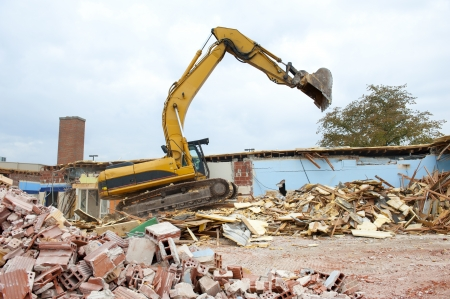 A large backhoe demolishes an old building Stock Photo - 23832368