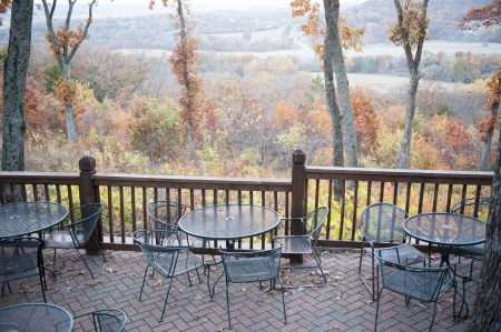 A public patio overlooks a scenic hill lined with trees covered in Autumn leaves