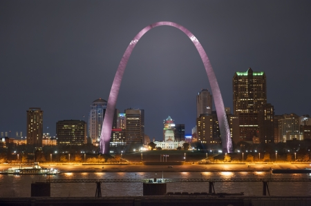 Night shot of downtown St  Louis riverfront with the Arch lit up pink for breast cancer awareness month, shot from the Illinois side of the river