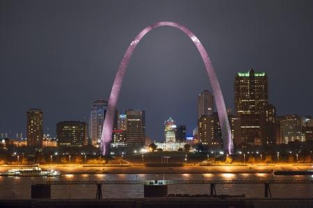 Nachtaufnahme der Innenstadt von St. Louis am Flussufer mit dem Bogen leuchtete Rosa für Brustkrebs-Bewusstseinsmonat, erschossen von der Illinois Seite des Flusses Standard-Bild - 24810357