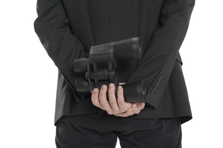 corporate espionage: Closeup of a man holding a pair of binoculars behind his back, isolated on white