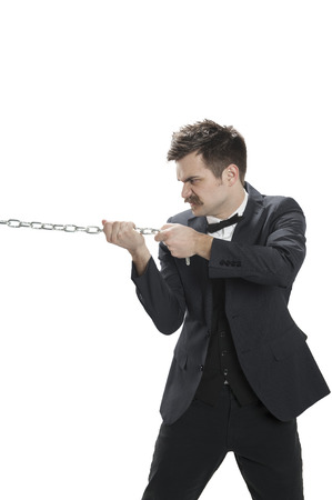 Man in a business suit pulls on a chain Stock Photo