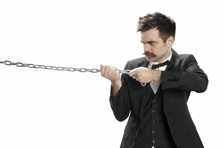 Young man in business suit and bowtie scowls and pulls on a strtong chain Stock Photo