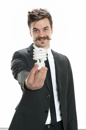 Young man in business suit holds a CFL compact fluorescent lightbulb