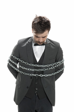 Attractive young man in business suit looks sullen as he stands with chains around him, isolated on white photo