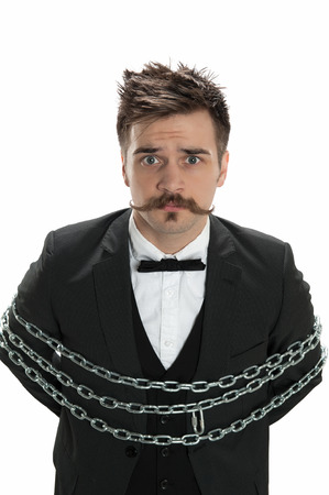 Attractive young man in business suit looks sullen as he stands with chains around him, isolated on white Stock Photo