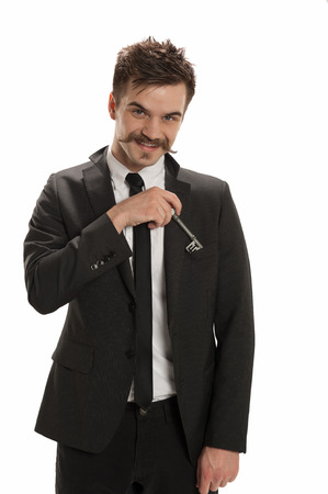 retrieves: Handsome young businessman retrieves a skeleton key from his lapel pocket, isolated on white background Stock Photo